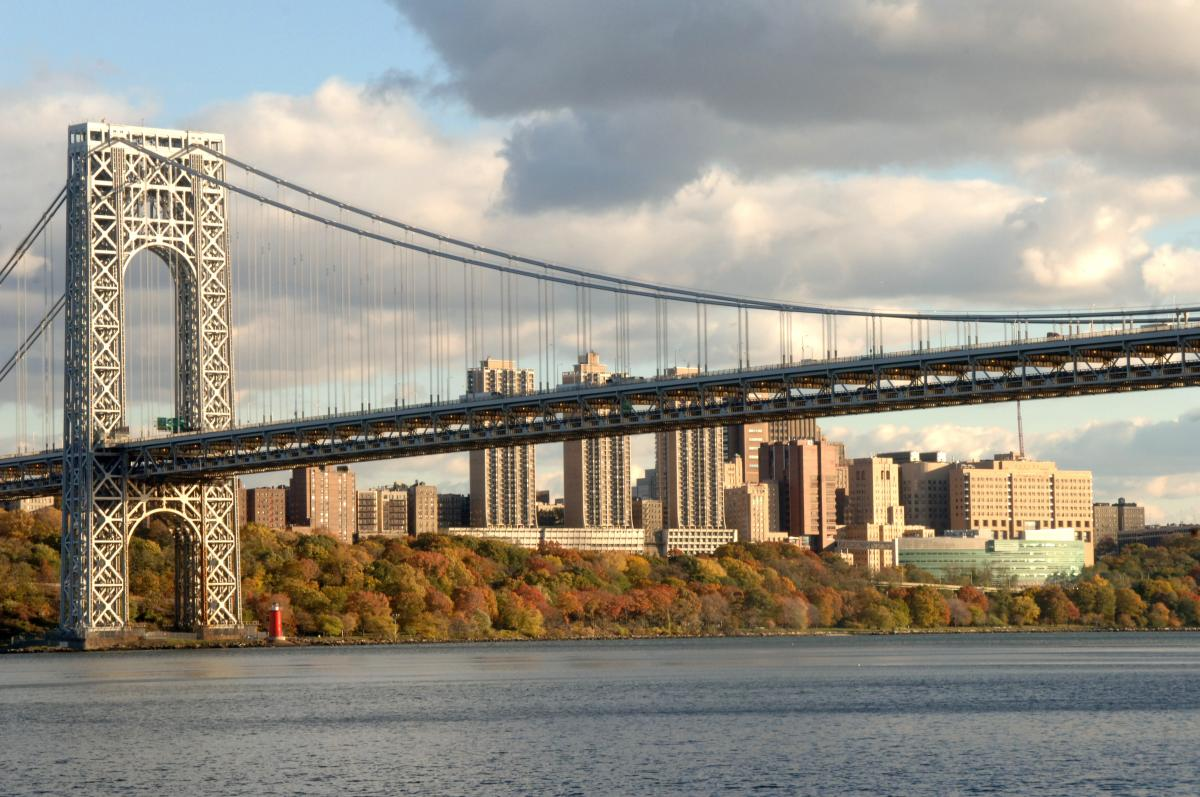 Photo of the George Washington bridge from the Jersey side in fall with Columbia University Medical Center in the background.