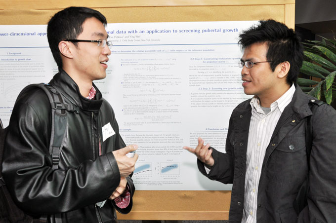 Two students talk in front of a poster presentation.